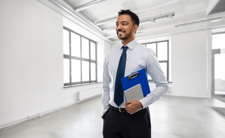 business, realty and people concept - smiling indian businessman or realtor with clipboard over empty office room background Imagens - 119079534