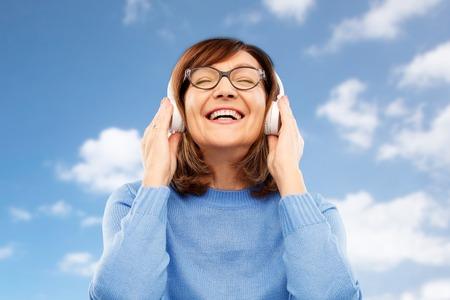 senior woman in headphones listening to music Stockfoto