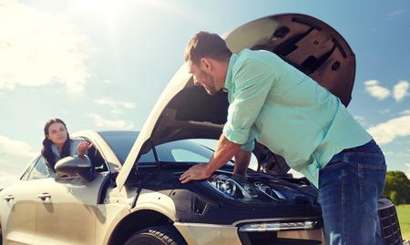 Paar mit offener Motorhaube eines kaputten Autos auf dem Land