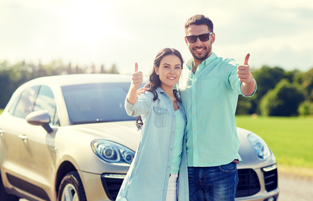 happy man and woman showing thumbs up at car
