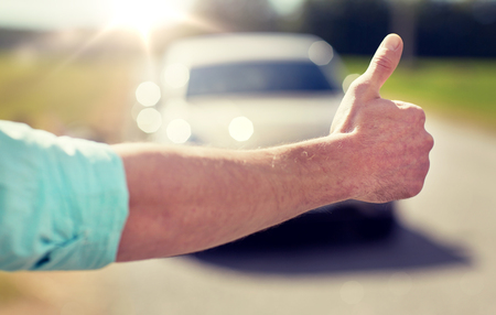 man hitchhiking and stopping car with thumbs up Imagens
