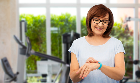 sport, old people and technology concept - smiling senior woman with fitness tracker over gym background Stock Photo
