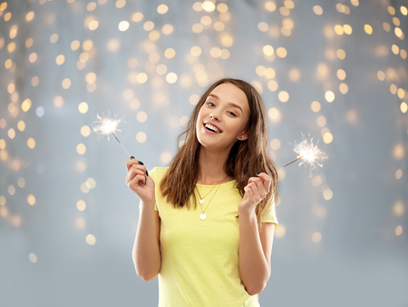 happy teenage girl with two sparklers over lights