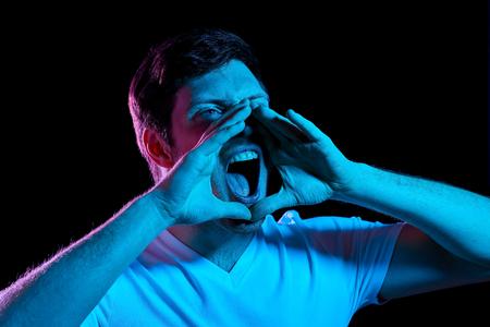homme en colère criant sur les néons dans une pièce sombre Banque d'images