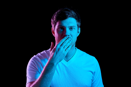 man covering his mouth by hand in neon lights