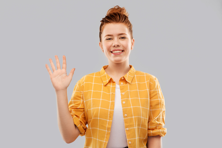 smiling red haired teenage girl waving hand