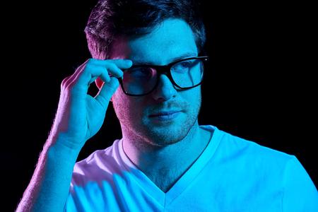 man in glasses over neon lights in dark room Zdjęcie Seryjne