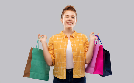 sale, outlet and people concept - smiling red haired teenage girl in checkered shirt with shopping bags over grey background