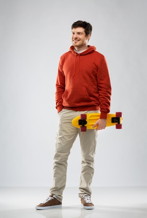 leisure, sport and people concept - happy smiling young man in hoodie with short skateboard over grey background