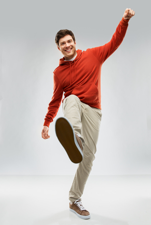 motion and people concept - smiling young man in red hoodie stepping up over grey background Stockfoto