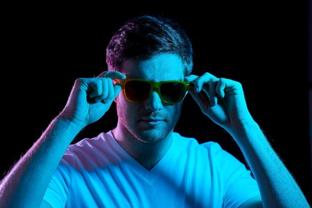 man in sunglasses over ultra violet neon lights