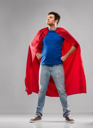 man in red superhero cape over grey background Reklamní fotografie