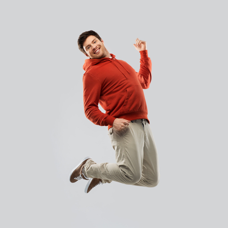 young man in hoodie jumping over grey background