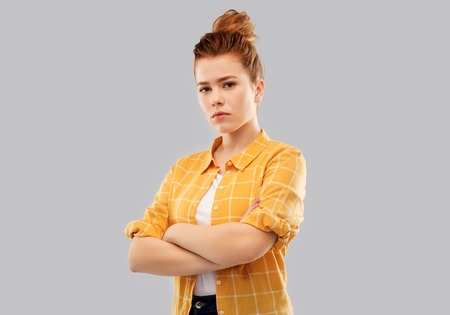 serious red haired teenage girl with crossed arms Stock Photo