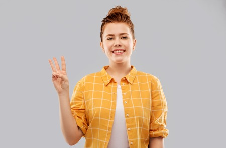red haired teenage girl showing three fingers Archivio Fotografico - 119125730