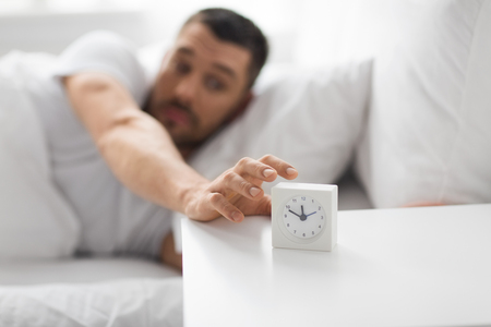 close up of man in bed reaching for alarm clock