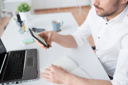 close up of businessman using smartphone at office