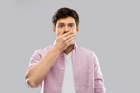 shocked young man covering his mouth by hand Stock Photo - 119164045