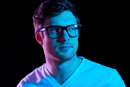 man in glasses over neon lights in dark room Stock Photo