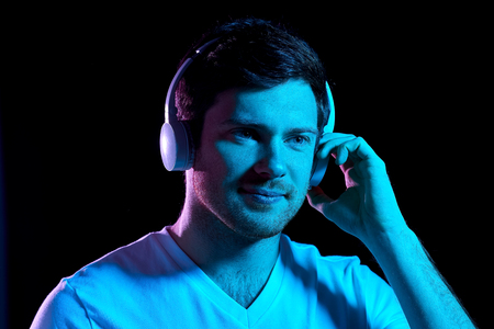 man in headphones over neon lights of night club Stock Photo