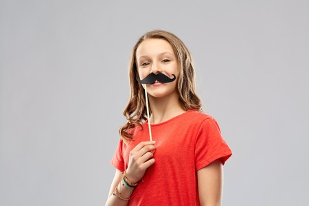 smiling teenage girl with mustaches party prop