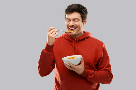 smiling young man in red hoodie eating cereals