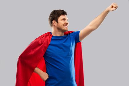 man in red superhero cape over grey background 版權商用圖片