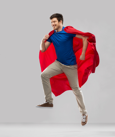 man in red superhero cape jumping in air Banque d'images - 119216062