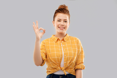 happy red haired teenage girl showing ok hand sign