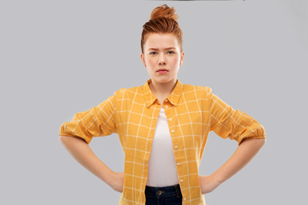serious red haired teenage girl with hands on hips