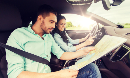 happy man and woman with road map driving in car Stockfoto