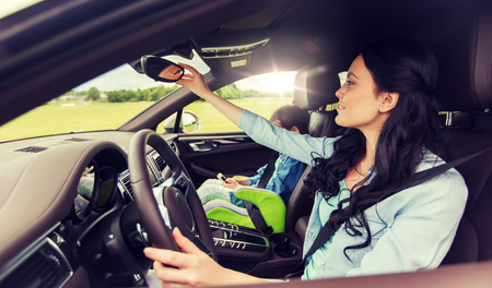 happy woman with little child driving in car Banco de Imagens