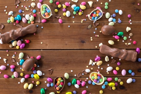 chocolate eggs, easter bunnies and candies on wood