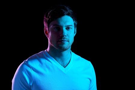 portrait of man over neon lights in dark room