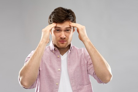 unhappy young man suffering from headache