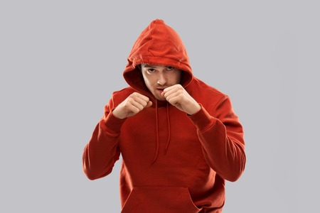 man in red hoodie fighting with fists or boxing