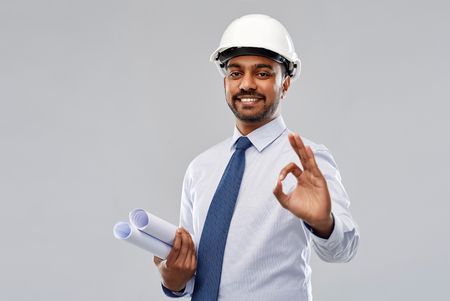 architect in helmet with blueprints showing ok