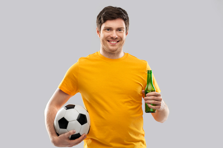 man or football fan with soccer ball and beer Фото со стока