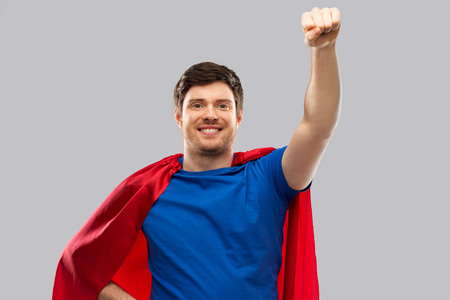 man in red superhero cape over grey background Stock Photo