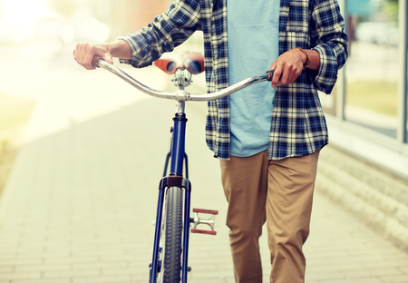 people, style and lifestyle concept - close up of young man with fixed gear bicycle walking along city street