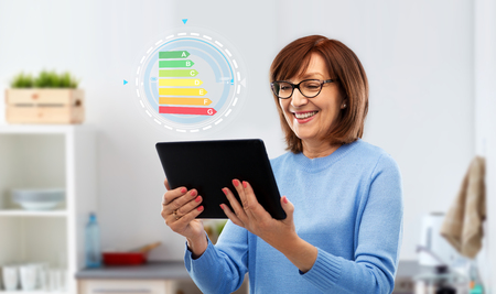 technology and efficiency concept - smiling senior woman in glasses using tablet computer with energy consumption chart over grey background