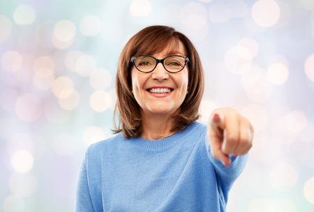 senior woman in glasses pointing finger to you