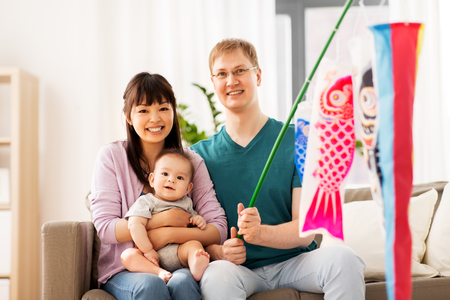 mixed-race family, childrens day and asian holidays concept - happy mother, father and baby son with koinobori carp streamer celebrating tango no sekku at home