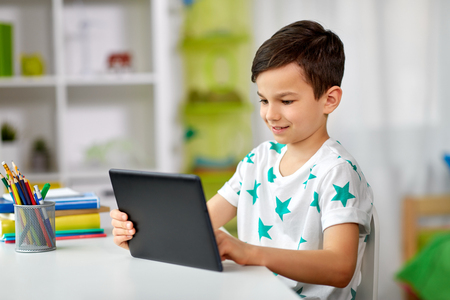 education, people and learning concept - happy student boy with tablet pc computer and notebook learning at home