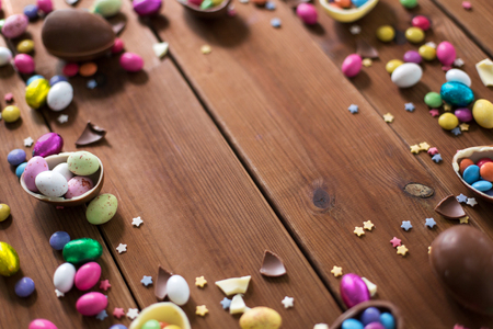 easter, sweets and confectionery concept - chocolate eggs and candy drops on wooden background