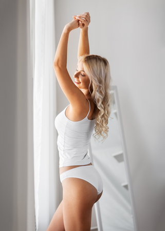 morning and people concept - happy young woman in white underwear stretching at home window