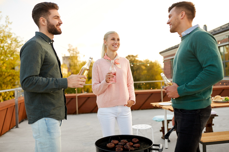 leisure and people concept - happy friends with bbq grill and non alcoholic drinks having barbecue party on rooftop