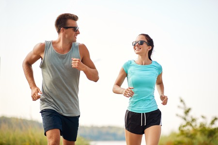 fitness, sport and lifestyle concept - happy couple in sports clothes and sunglasses running along summer beach
