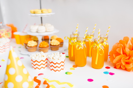 party drinks and food concept - close up of fruit juice or lemonade in decorated glass bottles with paper straws and popcorn