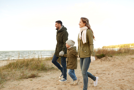 family, leisure and people concept - happy mother, father and little daughter walking along autumn beach 写真素材